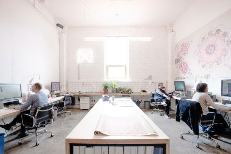 Bàn làm việc được kê sát tường, dọc theo chiều dài văn phòng. Ở giữa là một bàn trung tâm lớn có thể sử dụng khi nhóm